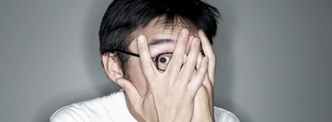 Asian male covering his face with his hands